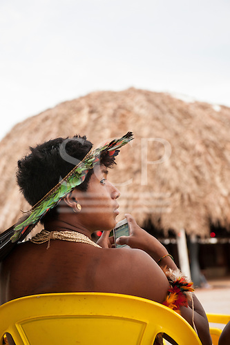 An indigenous Xerente Brazilian sits in a yellow plastic chair in front of the Knowledge House using his smart phone during the International Indigenous Games in Brazil. 27th October 2015