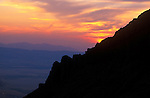 "The sun sets behind a rocky ridge on ""The helmet"" in the Madison Mountain Range near Ennis, Montana"