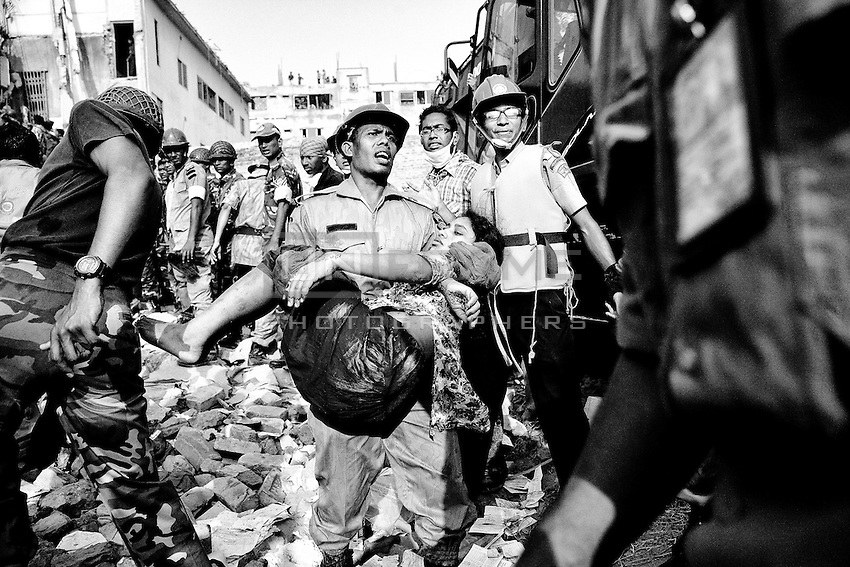 People rescue a garment worker, who was trapped under the collapsed Rana Plaza building in Savar, near Dhaka, Bangladesh