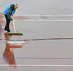 An official sweeps water off the track before women's pole vault competition can start<br /> <br /> Photographer Chris Vaughan/CameraSport<br /> <br /> 20th Commonwealth Games - Day 10 - Saturday 2nd August 2014 - Athletics - Hampden Park - Glasgow - UK