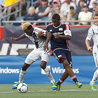LA Galaxy forward Gyasi Zardes (29) dribbles and encounters stiff defense by New England Revolution defender Andrew Farrell (2). In a Major League Soccer (MLS) match, the New England Revolution (blue) defeated LA Galaxy (white), 5-0, at Gillette Stadium on June 2, 2013.