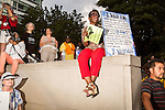 July 13, 2015. Winston Salem, North Carolina.<br />  Lisa Scott, of Kernersville , NC, awaits the start of the speeches to support the NC NAACP's voting rights case against Gov. Pat McCrory.<br />  To rally support for the North Carolina NAACP's case against Gov. Pat McCrory (NC NAACP v. McCrory), a march was held in downtown Winston Salem on the opening day of the case in federal court. Thousands gathered to walk the streets of downtown and listen to speeches proclaiming the importance of defeating new requirements for voter registration,<br />  The NC NAACP contests that HB 589 (Voter ID requirements) violate Section 2 of the Voting Rights Act (42 U.S.C. 1973) and the Fourteenth and Fifteenth Amendments of the Constitution.