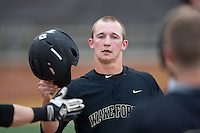 Drew Freedman (5) of the Wake Forest Demon Deacons is greeted by teammates after scoring a run against the Clemson Tigers at David F. Couch Ballpark on March 12, 2016 in Winston-Salem, North Carolina.  The Tigers defeated the Demon Deacons 6-5.  (Brian Westerholt/Four Seam Images)