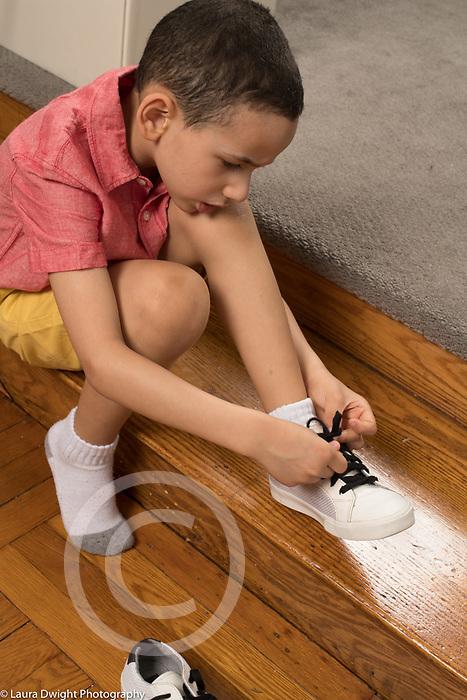 5 year old boy dressing self tying own shoe