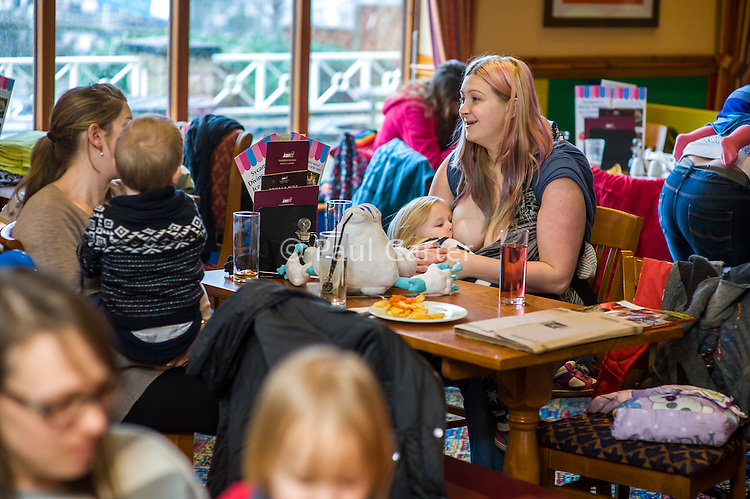 A mother sitting at a table talks to a friend as she breastfeeds her two year old daughter in the family restaurant and play area of a pub.<br /> <br /> Lancashire, England, UK<br /> <br /> Date Taken:<br /> 07-01-2015<br /> <br /> © Paul Carter / wdiip.co.uk
