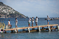 Men wait for a ride to their boats, anchored in background, on Sunday, Sept. 20, 2015, in Positano, Italy. (Photo by James Brosher)