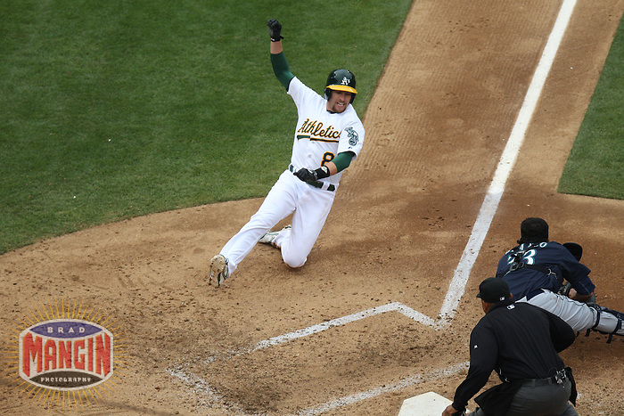 OAKLAND, CA - JUNE 15:  Jed Lowrie #8 of the Oakland Athletics slides home against the Seattle Mariners during the game at O.co Coliseum on Saturday June 15, 2013 in Oakland, California. Photo by Brad Mangin
