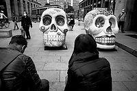 """Italy. Lombardy Region. Milan. Town center. Art exhibition. """" The skull parade"""". Two skulls artworks by (L) Silvia Cirri, """"Potere del Fiore"""" and (R) Marzia Etna, """"La muerte . è ...se vi pare"""". Silvia Cirri and Marzia Etna are both artists who did work for Viareggio Carnival. Teeth and bones. People in the street wear a mask on their faces to protect themselves from the Coronavirus (also called Covid-19). An old tram runs in the street. Milan (Italian: Milano) is a city in northern Italy, capital of Lombardy, and the second-most populous city in Italy .6.10.2020 © 2020 Didier Ruef"""