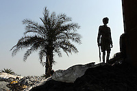 A young boy stands near large vats that are used for burning leather trimmings on the banks of the Ganges River in Kanpur. The city is notorious for having some of the country's worst pollution which is created by the local leathery tannery industry.
