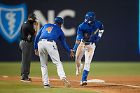 Vidal Brujan (2) of the Durham Bulls slaps hands with third base coach Brady Williams (4) after hitting a home run against the Jacksonville Jumbo Shrimp at Durham Bulls Athletic Park on May 15, 2021 in Durham, North Carolina. (Brian Westerholt/Four Seam Images)