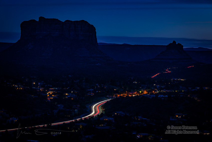 December Twilight in Sedona ©2018 James D Peterson.  From the southeast side of Airport Mesa, this is the view towards Courthouse Butte and Bell Rock. This 30 second exposure turns the cars on Highway 179 into a beautiful S-curve in the foreground.  The southbound lane of 179 can be seen beneath Bell Rock in the distance.