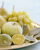 Decorative frosted fruit presented on a silver tray glisten in the candlelight