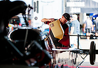 Aug 9, 2020; Clermont, Indiana, USA; A crew member for NHRA top fuel driver Steve Torrence (not pictured) pours nitromethane race fuel into the fuel tank of the dragster in the pits during the Indy Nationals at Lucas Oil Raceway. Mandatory Credit: Mark J. Rebilas-USA TODAY Sports