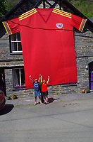 """Pictured: Lynne Humphreys-McCrickett (R) with husband John McCrickett by the 8m x 5m Wales football shirt in Dinas Mawddwy, Gwynedd, north Wales, UK.<br /> Re: Lynne Humphreys-McCrickett has created a 8m x 5m football shirt and displaying it on the side of her house at Minllyn in Dinas Mawddwy, Gwynedd, north Wales, UK.<br /> She said: """"We originally created it in 2016 because there were not any fan zones in north Wales, there certainly weren't any where we are,"""" Lynne said. """"Our neighbour is a football fan too so we were like we will make our own fan zone.""""<br /> Lynne, 50, and her husband John McCrickett, 54, are massive football fans and set about creating the shirt together, which they have dubbed 'Y Crys Mawr Coch', meaning the big red shirt.<br /> Having trained as a seamstress with Laura Ashley when she was just 16, studied at London College of Fashion and having worked as a pattern cutter in London for 20 years, she certainly has the skills for it."""