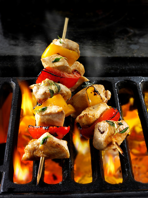 Chicken skewers being cooked over open flames. Food photos, pictures & images.