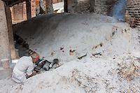 Bhaktapur, Nepal.  Potter at Work Tending his Kiln in Potters' Square.