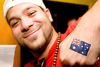 Australia fan E. Clark shows off a temporary tattoo of an Australian flag after his team's World Cup match with Croatia on June 22, 2006 at the Sunburnt Cow, a bar in New York City.<br /> <br /> The World Cup, held every four years in different locales, is the world's pre-eminent sports tournament in the world's most popular sport, soccer (or football, as most of the world calls it).  Qualification for the World Cup is open to any country with a national team accredited by FIFA, world soccer's governing body. The first World Cup, organized by FIFA in response to the popularity of the first Olympic Games' soccer tournaments, was held in 1930 in Uruguay and was participated in by 13 nations.    <br /> <br /> As of 2010 there are 208 such teams.  The final field of the World Cup is narrowed down to 32 national teams in the three years preceding the tournament, with each region of the world allotted a specific number of spots.  <br /> <br /> The World Cup is the most widely regularly watched event in the world, with soccer teams being a source of national pride.  In most nations, the whole country is at a standstill when their team is playing in the tournament, everyone's eyes glued to their televisions or their ears to the radio, to see if their team will prevail.  While the United States in general is a conspicuous exception to the grip of World Cup fever there is one city that is a rather large exception to that rule.  In New York City, the most diverse city in a nation of immigrants, the melting pot that is America is on full display as fans of all nations gather in all possible venues to watch their teams and celebrate where they have come from.