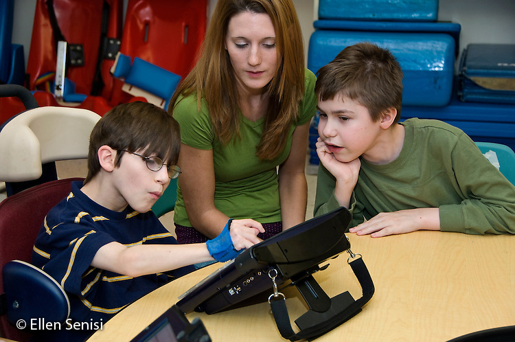 MR / Albany, NY.Langan School at Center for Disability Services .Ungraded private school which serves individuals with multiple disabilities.Boy (boy, 9, cerebral palsy, limited verbal output with expressive and receptive language delays) uses alternative and augmentative communication device during speech and language development lesson. Student intern and another student (boy, 10, Duchenne muscular dystrophy, expressive and receptive language delays) watch. He is wearing hand splints to help him isolate his thumbs which helps him use the device more easily..MR: Rub1, Bud2, Chm.© Ellen B. Senisi