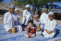 Mudayrib, Oman, Arabian Perninsula, Middle East - These Omani men and boys are sitting on a hillside to watch camel races taking place down below.  All are wearing the traditional men's robe, a dishdasha.  Boys wear the traditional embroidered hat, the kumma; men wear the traditional turban, the msarr or massar.  Boys hold gifts they have received for the Eid al-Adha (Feast of the Sacrifice), the annual feast through which Muslims commemorate God's mercy in allowing Abraham to sacrifice a ram instead of his son, to prove his faith.