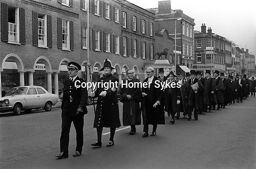 """The Beadle leads local dignitaries to the Weighing the Mayor ceremony. At the start of his or term of office and again at the end is a custom unique to High Wycombe. It is thought the tradition started to ensure the mayor and other officials did not """"live off the fat of the land"""" at the expense of the ratepayers. <br /> The weighing is held in the High Street on huge scales and various dignitaries are weighed in addition to the councillors. It is traditional for the crowd to jeer when the person is declared to weigh so many pounds """"and some more"""" and for the crowd to cheer if it is """"and no more"""". <br />  My ref 1/736/1971"""