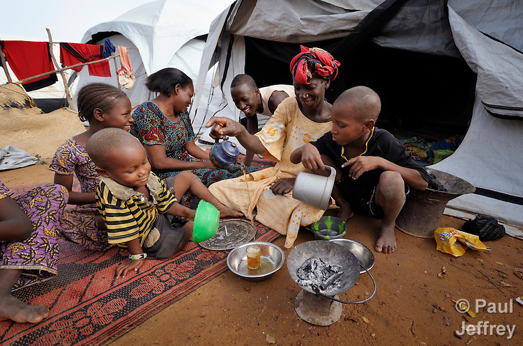 A family sits in front of their tent in a camp in Mopti, Mali, for people displaced by the fighting in the north of the country. Islamist rebels seized control of the north of Mali in 2012, but were chased out in early 2013 by French troops. Many displaced and refugee families have yet to return, preferring to wait for better security and improved economic conditions in the north.