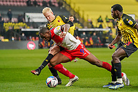 Uche Ikpeazu of Wycombe Wanderers (centre) is tackled by Garath McCleary of Wycombe Wanderers during the Sky Bet Championship behind closed doors match between Watford and Wycombe Wanderers at Vicarage Road, Watford, England on 3 March 2021. Photo by David Horn.