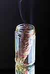 Bundle of sage as smudge or incense burning in jar on black background.