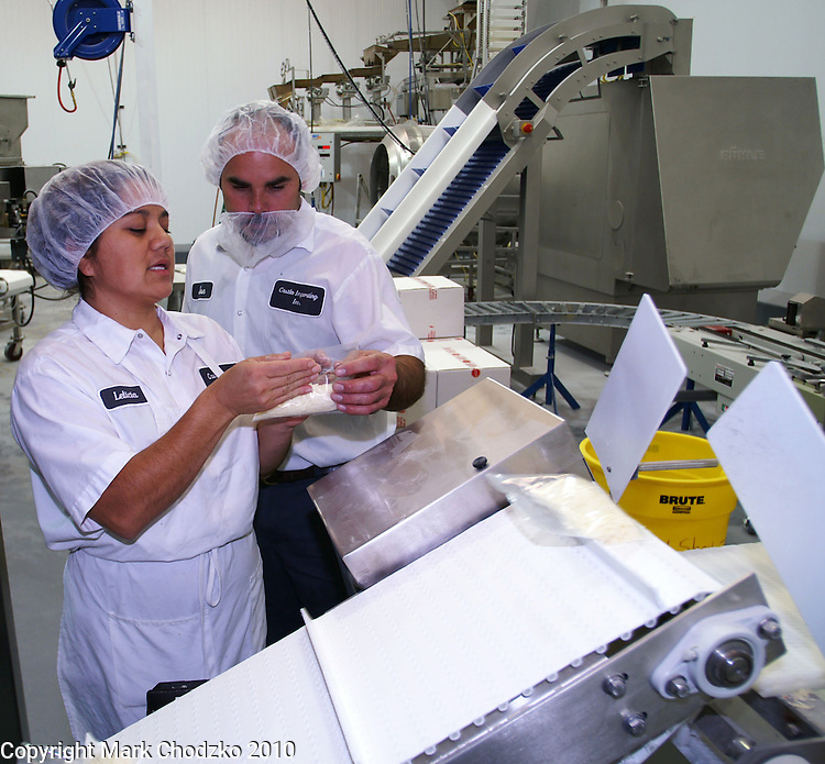 Workers in cheese factory inspect products at Castle Importing.