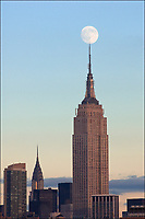 Empire State Building with a full moon right on top at sunset, Chrysler Building is in the background. Real capture, not a digital composite.