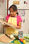 9 year old girl learning to cook looking at cookbook with ingredients on table nearby Mexican dish using cactus, onion, beans and tomatoes