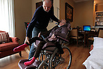 William Massart settles his daughter Sandra Massart, 10, in a wheelchair at the family's apartment in Durham, NC, USA, on Tuesday, Feb. 14, 2012.  Sandra Massart is being treated for MLD, a degenerative condition.  Photo by Ted Richardson