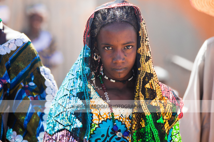 Dressed in her finest clothing, Dicko Hadjiratou, age 14, browses the weekly Fulani market in the town of Djibo in northern Burkina Faso.