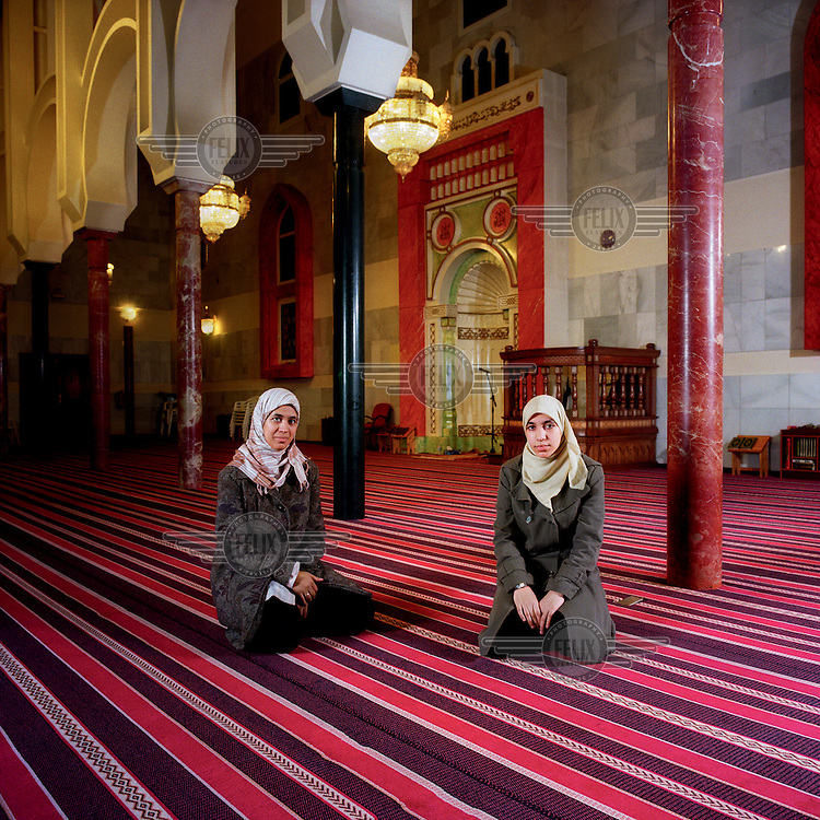 Sisters Maryam and Saadia Benkhafa kneel inside Mezquita M.30 mosque, the largest mosque in Madrid.