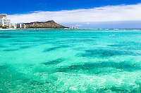 A view of Waikiki with Diamond Head Crater in the distance on O'ahu; a single surfer sets out to catch some waves past reef-strewn waters.