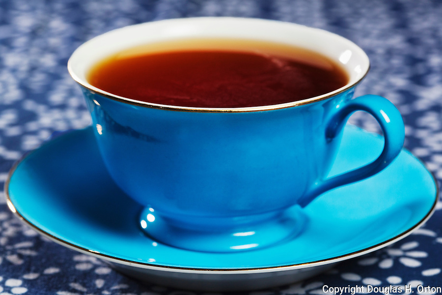 Cup of tea on blue table cloth.  Blue China cup.  Gold leaf. Blue Table Cloth.