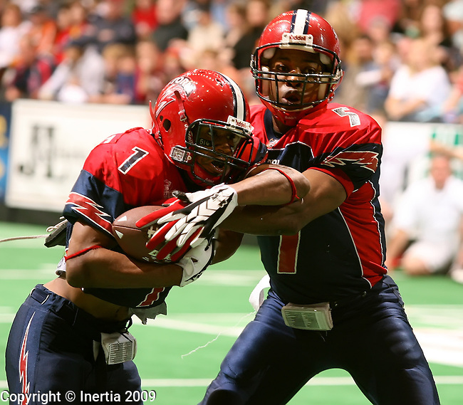 SIOUX FALLS, SD - MAY 16: Sean Treasure #1 of the Sioux Falls Storm takes the hand off from quarterback Terrance Bryant #7 against the Wichita Wild in the second quarter of their game Saturday night at the Sioux Falls Arena. (Photo by Dave Eggen/Inertia).