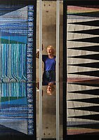BNPS.co.uk (01202) 558833<br /> Pic: ZacharyCulpin/BNPS<br /> <br /> 8 million stitches, 1 Holy Exhibition<br /> <br /> Pictured: Reflected in the Cathedral Font, Artist Jacqui Parkinson with embroideries entitled, 'God spoke – water!' (pictured left) and 'God spoke – light!'<br /> <br /> Twelve large embroidered panels fashioned from eight million stitches which tell the story of 'the Creation' have gone on display at Salisbury Cathedral.<br /> <br /> The panels, which measure up to 8ft by 11ft, are made from silk, hand-dyed materials, gold leaf and metallic leathers.<br /> <br /> They have been created by Devon-based textile artist Jacqui Parkinson who has dedicated three years to the solo project.<br /> <br /> The panels are inspired by the poetic verses of Genesis, the first book in the Bible, and include depictions of the Garden of Eden.