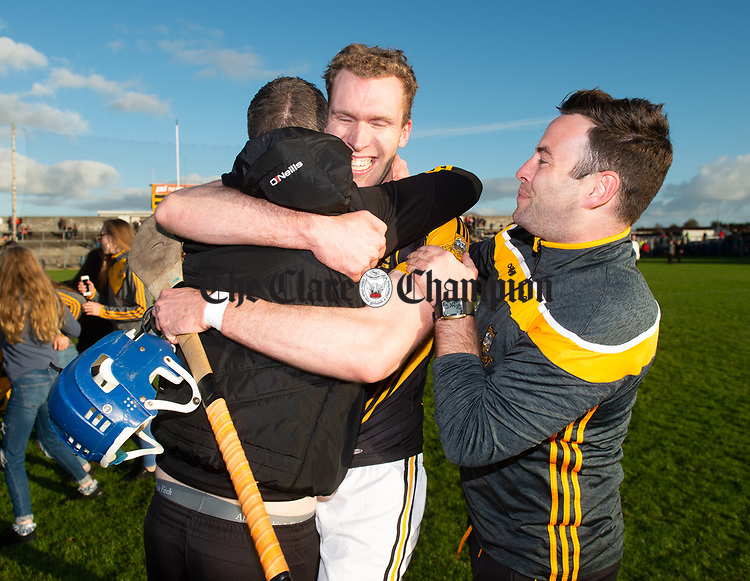 Aonghus Keane of Ballyea is hugged by manager Kevin Sheehan watched by mentor Barry Coffey following the county senior hurling final against Cratloe at Cusack Park. Photograph by John Kelly.
