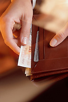 A hand taking British pounds out of a wallet.
