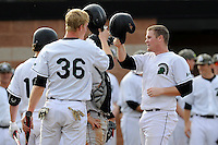 Third baseman Jake Beaver (11) of the University of South Carolina Upstate Spartans, right, is congratulated at home plater by catcher Charlie Carpenter (36) after scoring a run  in a game against the Winthrop University Eagles on Wednesday, March 4, 2015, at Cleveland S. Harley Park in Spartanburg, South Carolina. Upstate won, 12-3. (Tom Priddy/Four Seam Images)