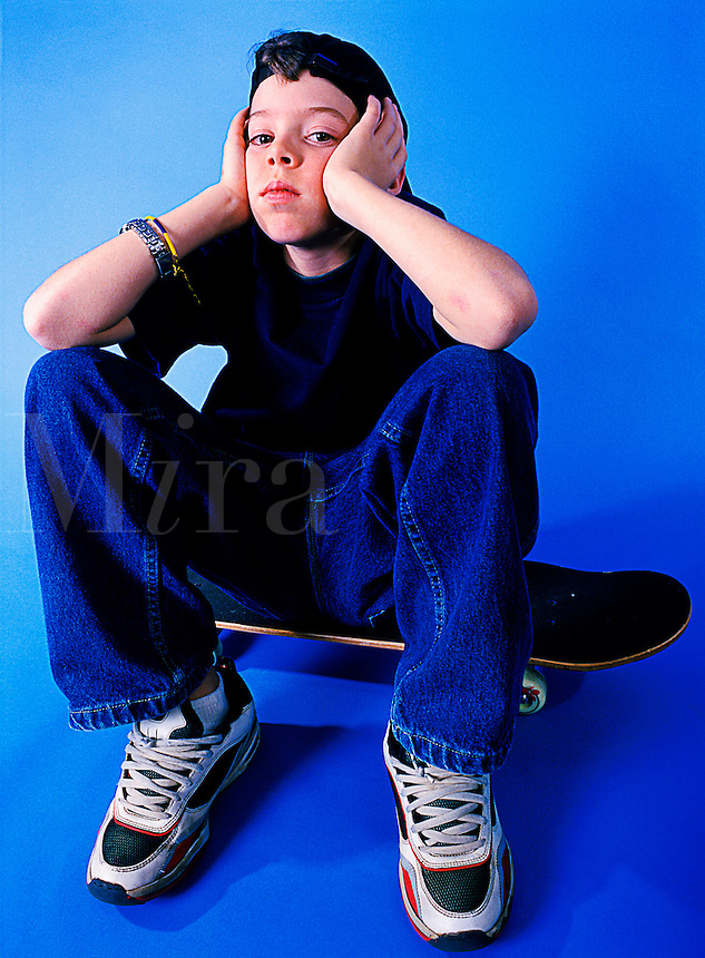 Young teenager boy sitting on a skateboard showing attitude.