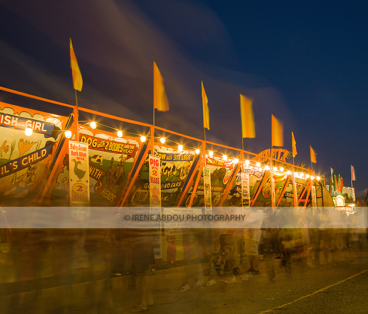 A longer shutter speed (4.0 seconds) renders the people walking along this carnival game strip at the Montgomery County Agricultural Fair into ghostly streaks and blurs. The streaks in the sky are also people walking past the camera, as the tripod was set at a fairly low level, aiming upwards.
