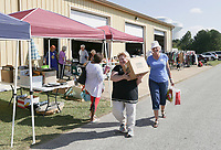 """Volunteer Debbie Dillier (right) helps Renita Riggs of Rogers (left) carry items out to her car, Thursday, October 7, 2021 during a rummage sale at the Central United Methodist Church in Rogers. The annual event returns with a larger selection for shoppers following a break due to the covid-19 pandemic. """"We're inundated this year,"""" said Carol Hartman, president of the  Central United Methodist Women. """"[donors] stayed home and cleaned out their houses, and so they had lots to donate this year."""" Items included houseware and clothing as well as unique items like an armoire of clothing from the 1880's and a Gucci watch. All funds from the sale will go to support projects for women and children in the community and world wide. Check out nwaonline.com/211008Daily/ for today's photo gallery. <br /> (NWA Democrat-Gazette/Charlie Kaijo)"""