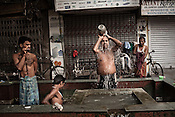 Street dwellers wash themselves on the streets of Kolkata in West Bengal, India.