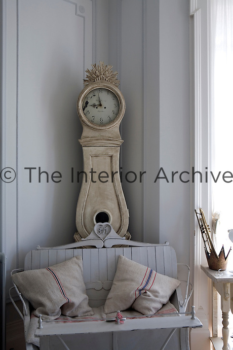 An antique Swedish sleigh has been turned into a couch and occupies a corner of the living room in front of a Mora clock