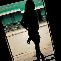 A Salvadorean sex worker, standing in the bar door, look out for clients in the street of San Salvador, El Salvador, 18 December 2013.