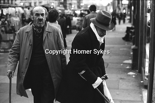 Old age pensioner OAP with stick walking past a disabled tramp who is using crutches,  Whitechapel market, East London, England 1975