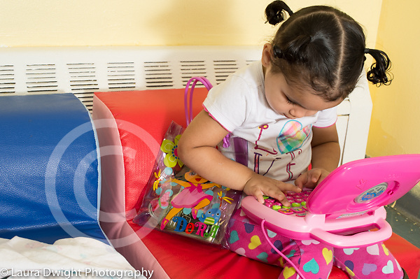 Education Preschool Two year olds girl playing with toy plastic computer