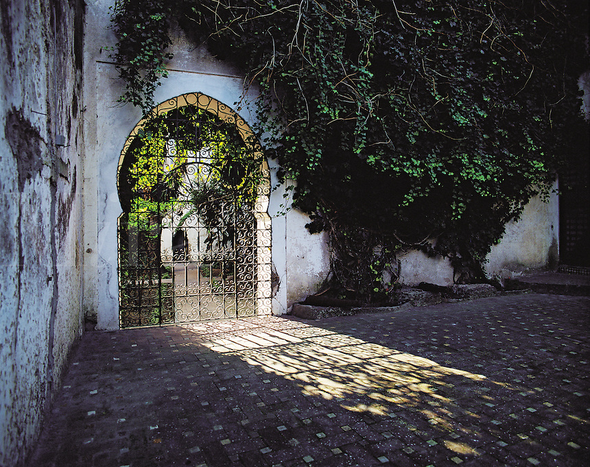 Arched gateway allowing shafts of sunlight into shadowed courtyard in Tangiers, Morocc