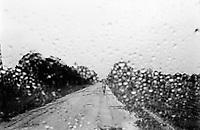 Angola. Province of Huambo. Huambo. A woman walks on a concrete road under the rain. Rainy season through a car's windshield. © 2000 Didier Ruef